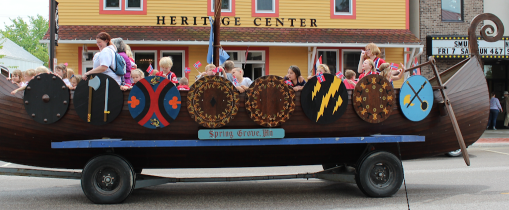 A viking ship on wheels passes in front of the Heritage Center, a large yellow building. In it ride an assortment of young children waving small Norwegian flags, as well as a few adults, smiling.