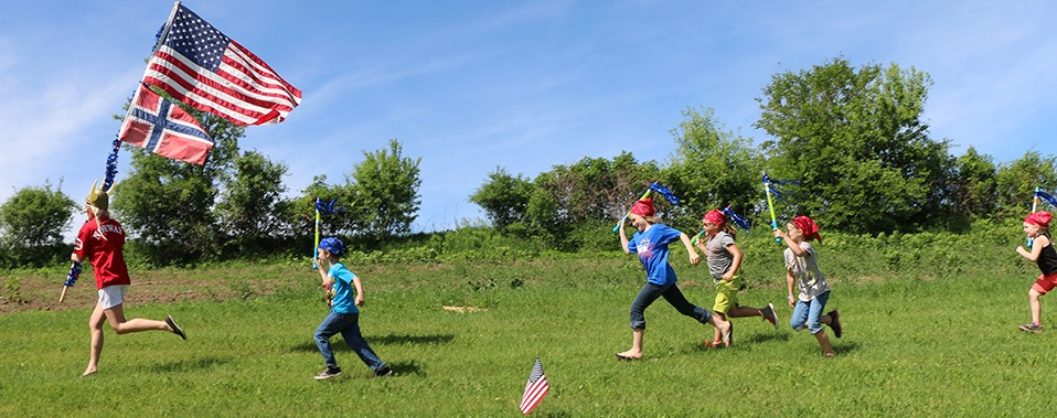 """A woman in a viking helmet and red shirt that reads """"Norway"""" on the back runs across the image to the left. She is carrying a Norwegian and American Flag. Five smiling children carrying water squirters run after her."""